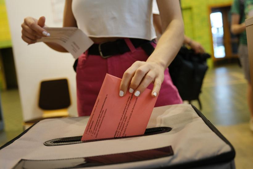 Wahlscheine verschwinden in Wahlurnen